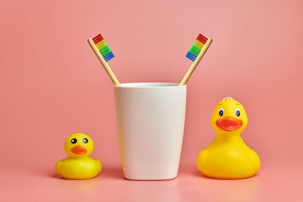 Dois brinquedos de escova de dentes e pato de banheiro. conceito de cuidados pessoais lgbt. protege a cavidade oral, remove a placa bacteriana e o tártaro.