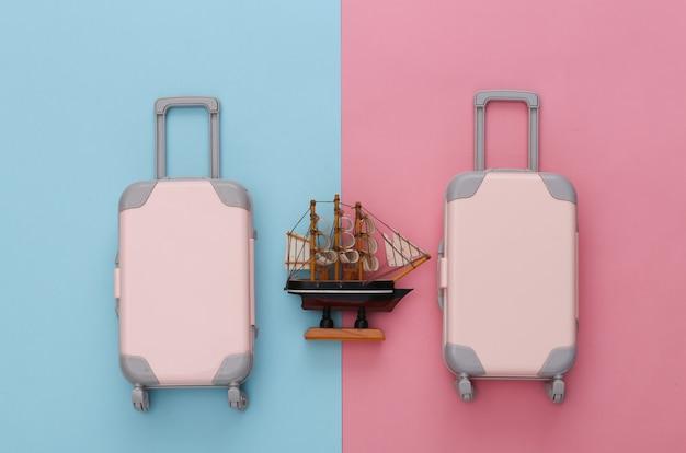 Dois brinquedos viajam bagagem e navio em pastel azul rosa. planejamento de viagens