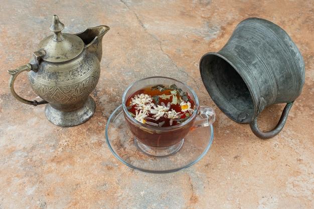 Dois bules antigos com chá de ervas no fundo de mármore