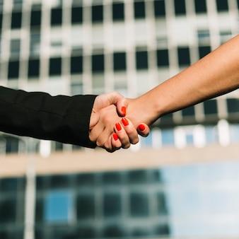 Dois, businesspeople, apertar mão, com, azul, predios, em, fundo