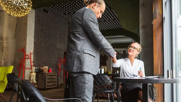 Dois, businesspeople, apertar mão, em, restaurante