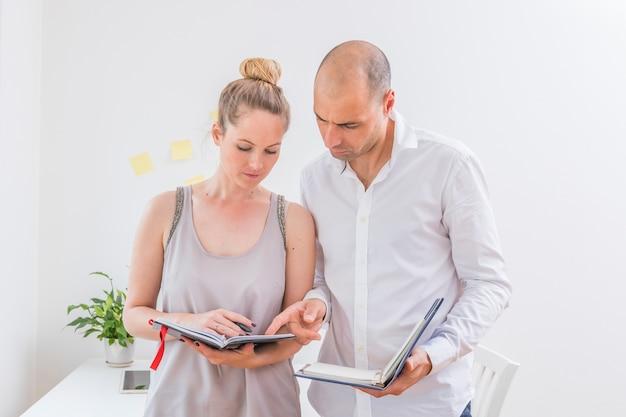 Dois, businesspeople, discutir, cronograma, em, diário, em, local trabalho