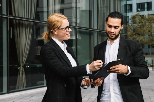 Dois, businesspeople, discutir, projeto negócio, sobre, área de transferência, em, ao ar livre