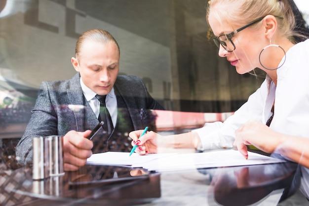 Dois, businesspeople, examinando, documento, em, restaurante