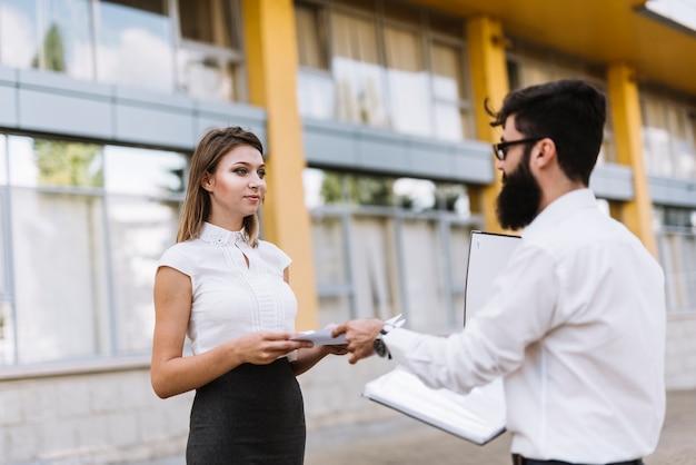Dois, businesspeople, ficar, exterior, escritório, dar, documentos