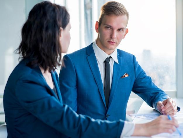 Dois, businesspeople, olhando um ao outro, em, escritório