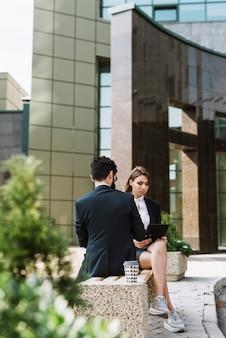 Dois, businesspeople, sentando, ligado, banco, exterior, a, edifício escritório