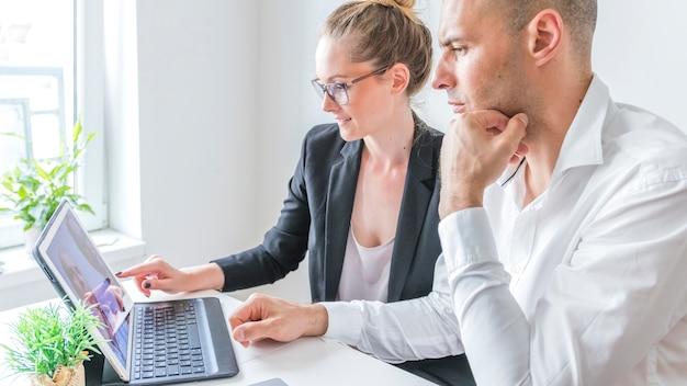 Dois, businesspeople, trabalhando, laptop, local trabalho