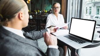 Dois, businesspeople, trabalhando, ligado, documento, com, laptop, escrivaninha