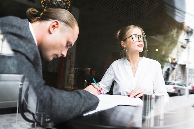 Dois, businesspeople, trabalhando, ligado, documento, em, restaurante