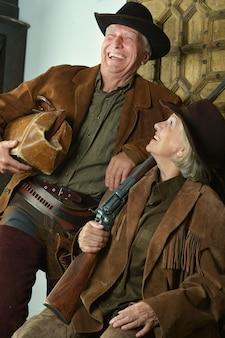 Dois caçadores sorridentes com roupas do oeste, closeup