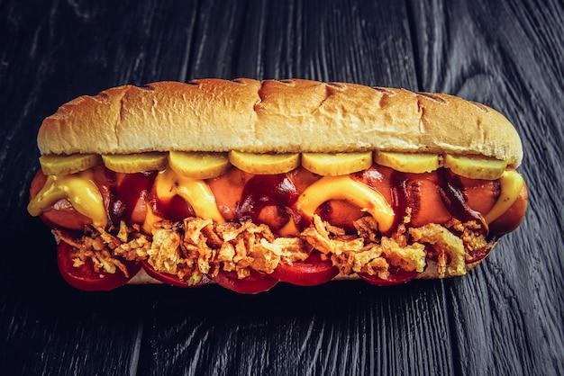 Dois cachorros-quentes com closeup de ketchup, mostarda amarela e cebola na superfície de madeira cinza.