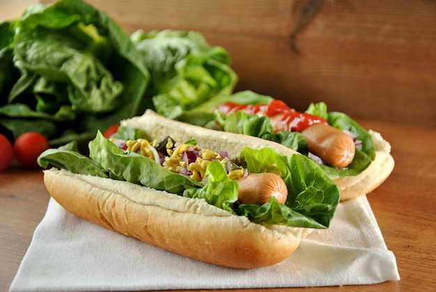 Dois cachorros-quentes com salada, cebola e molho