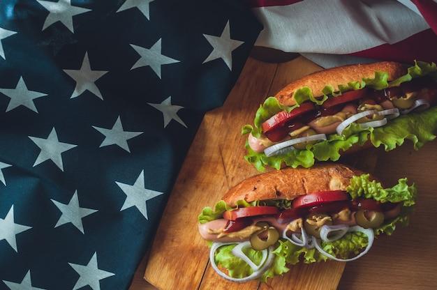 Dois cachorros-quentes em uma placa de madeira, óculos com cola e bandeira americana