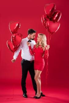 Dois cachos de balões segurados por jovem casal