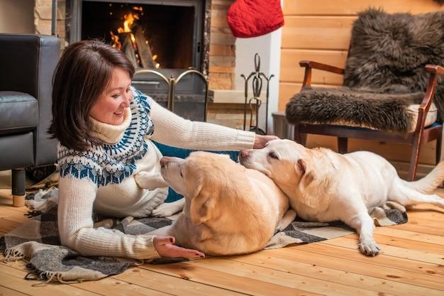 Dois cães retriever labrador dourado deitam-se com uma mulher asiática de meia-idade em um cobertor em frente a uma lareira de casa de campo.