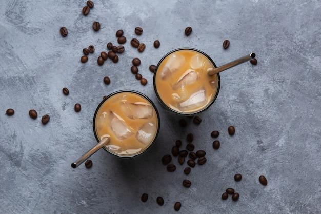 Dois café frio em um copo de vidro com um canudo de metal, grãos de café em um espaço cinza de concreto