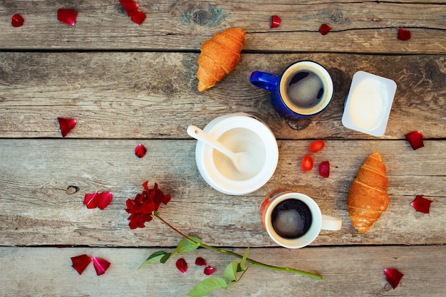Dois cafés, croissants, açúcar, doces, iogurte, rosa e pétalas na madeira velha