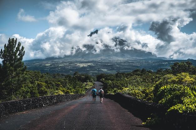 Dois caminhantes andando em uma estrada estreita, rodeada por vegetação com montanha nublada