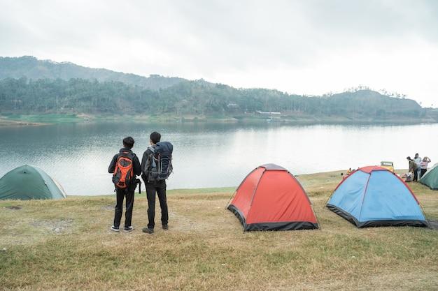 Dois caminhantes de homem em pé perto da tenda
