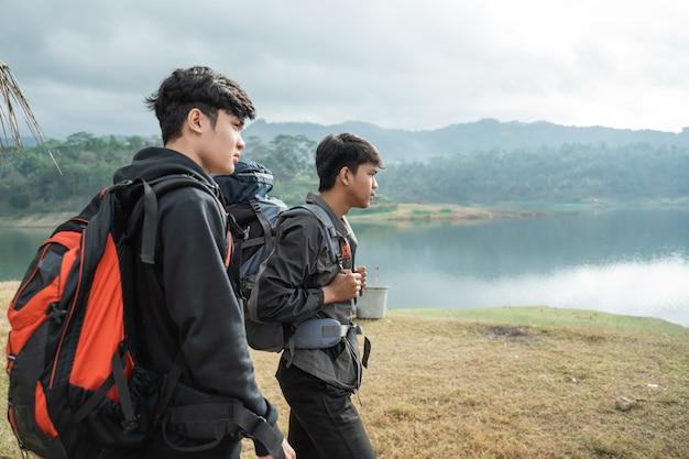 Dois caminhantes de homem trekking perto do lago