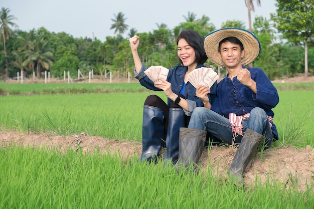 Dois camponeses e camponeses asiáticos vestidos em trajes tradicionais estão alegremente segurando notas de banco e levantando as mãos em um campo.