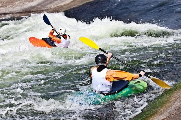 Dois canoístas ativos estão rolando e surfando em águas agitadas