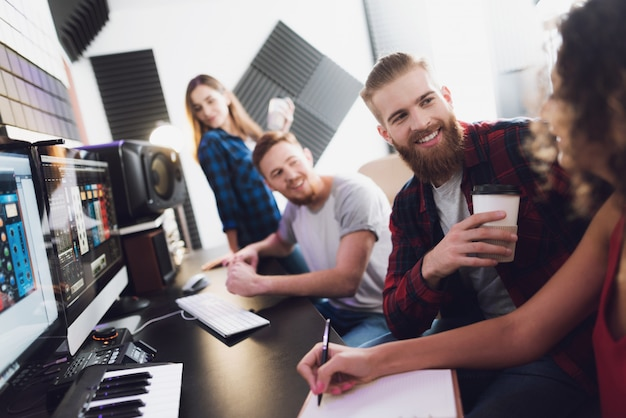 Dois cantores e engenheiros de som no estúdio de gravação.