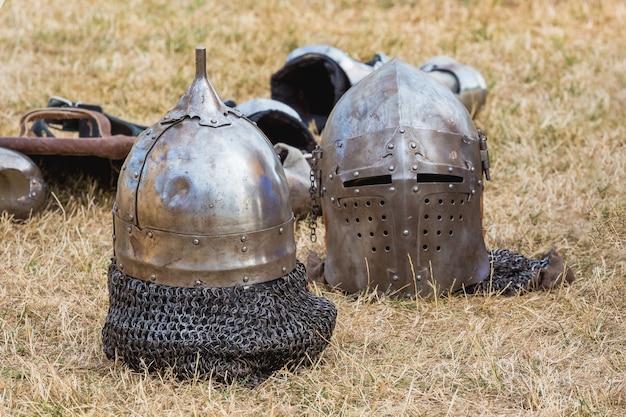 Dois capacetes de cavaleiro na grama no intervalo entre as lutas_