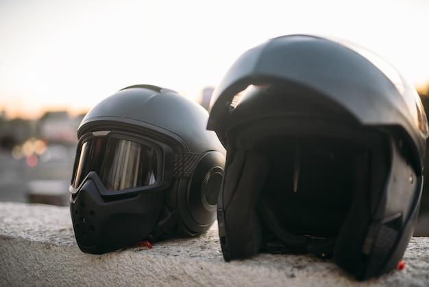 Dois capacetes de motociclista com óculos escuros e viseira na vista panorâmica do parapeito de concreto, ninguém, conceito de ciclismo
