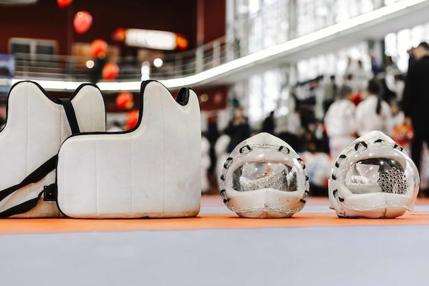 Dois capacetes de proteção brancos com máscara de plástico transparente e coletes para artes marciais no chão