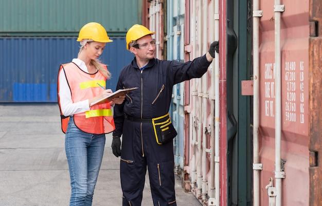 Dois capatazes abrindo a porta da caixa de contêineres para verificar produtos no transporte de contêineres de carga