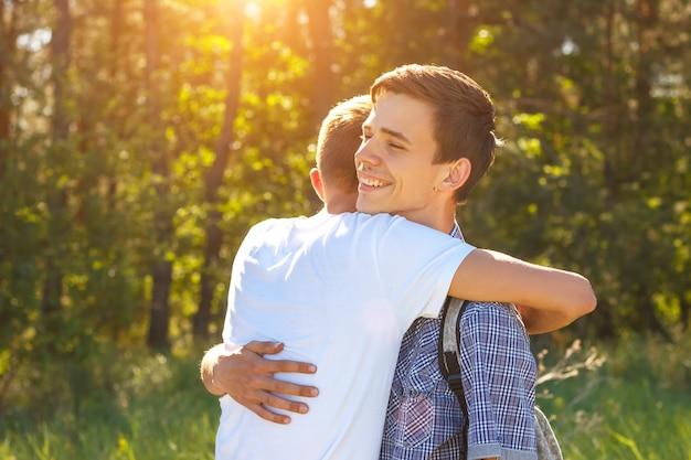 Dois caras abraçando em um dia ensolarado