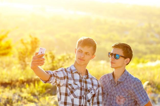 Dois caras bonitos tiram selfies amigos felizes são fotografados no telefone