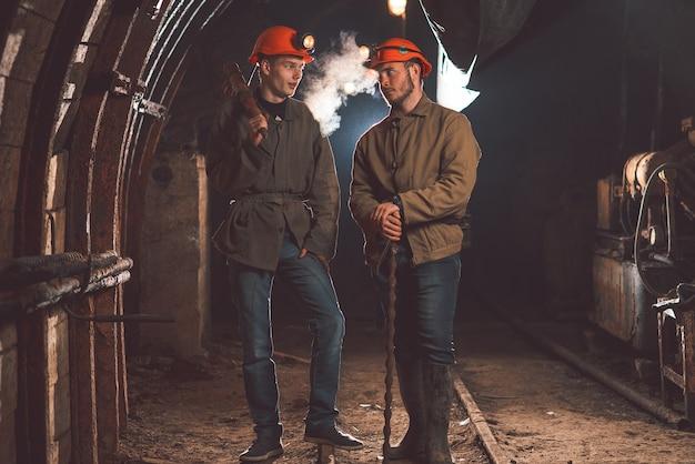 Dois caras com roupas especiais e capacetes de pé na mina. mineiros