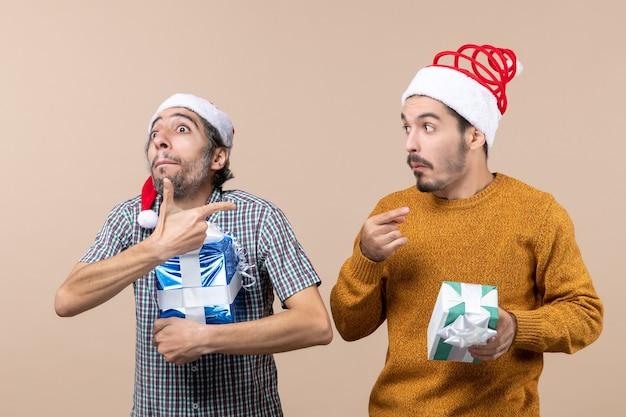Dois caras confusos apontam o dedo mostrando algo e segurando presentes de natal em um fundo bege isolado.