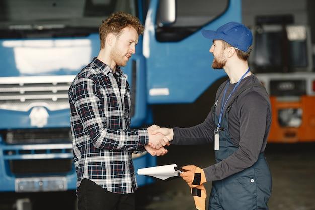 Dois caras conversando sobre trabalho. trabalho na garagem perto do caminhão. transferência de documentos com mercadorias
