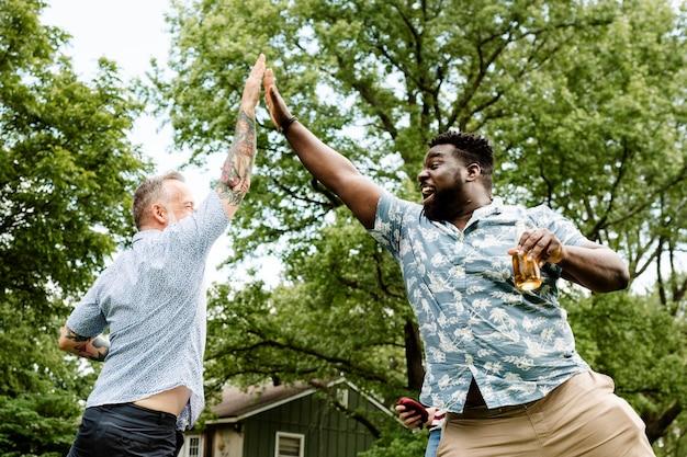 Dois caras dando mais um para o outro em uma festa de verão