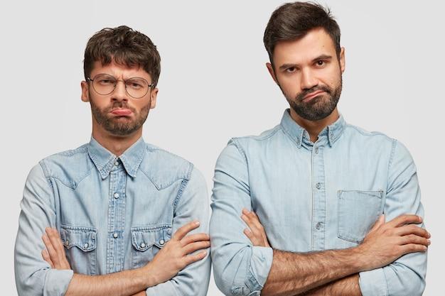 Dois caras descontentes mantêm os braços cruzados, olham com expressão taciturna, sentem-se perdidos depois de perder o jogo, vestidos com roupas jeans da moda, ficam um ao lado do outro sobre a parede branca.