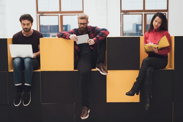 Dois caras e uma garota estão sentados em móveis modernos.