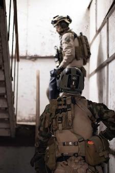 Dois caras em uniforme militar americano em pé na escada jogo de esportes airsoft forças militares simu