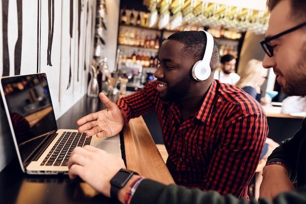 Dois caras estão sentados no bar com um computador.