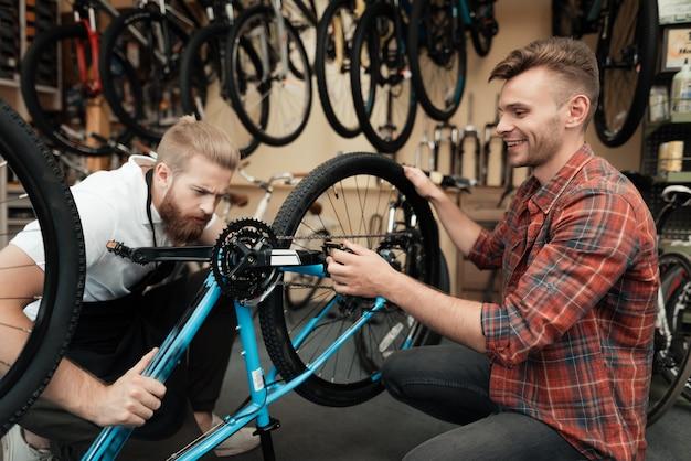 Dois caras examinam a bicicleta na oficina de esporte
