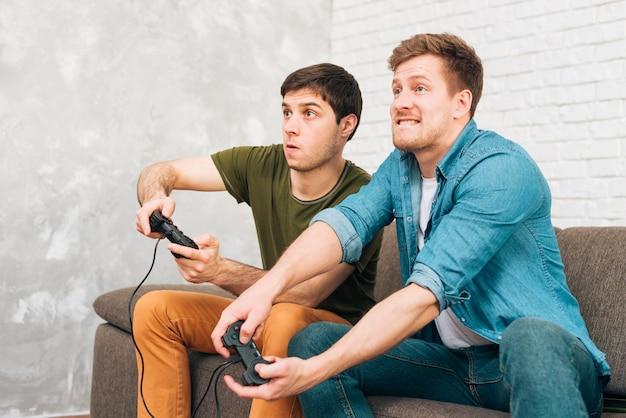 Dois caras jogando no console sentado no sofá