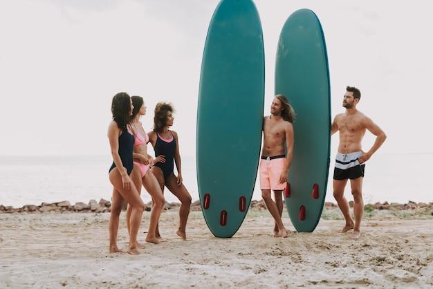 Dois caras na praia detém surf. meninas em maiôs.