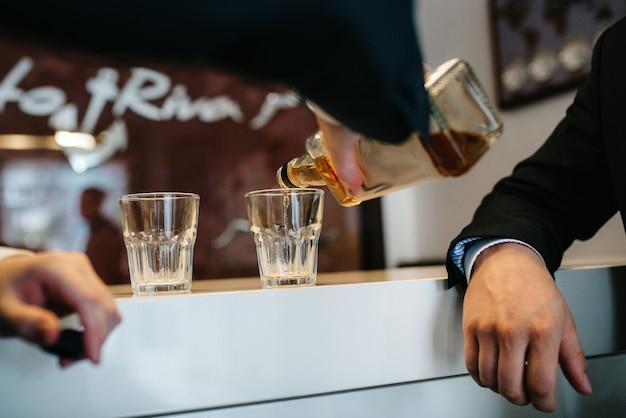 Dois caras no bar bebem uísque em taças de cristal