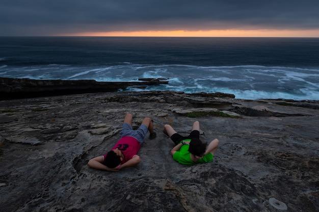 Dois caras olhando o pôr do sol na costa da montanha jaizkibel, ao lado de hondarribia, país basco.