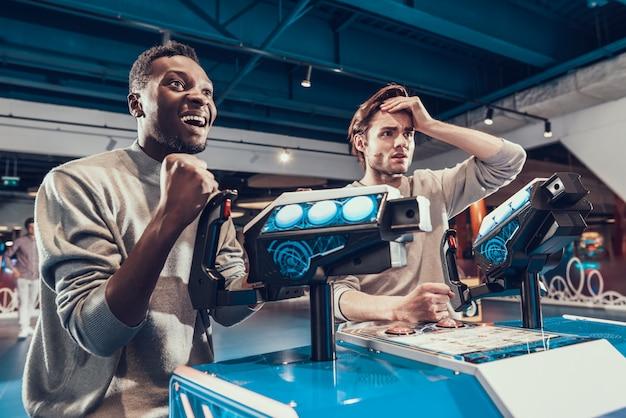 Dois caras pilotando naves espaciais na arcada.