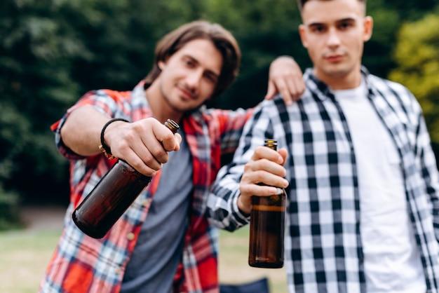Dois caras segurando uma cerveja e mostrando na câmera no acampamento. - imagem