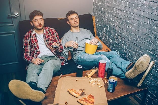 Dois caras sentados no sofá e segurando um pouco de comida e bebidas nas mãos